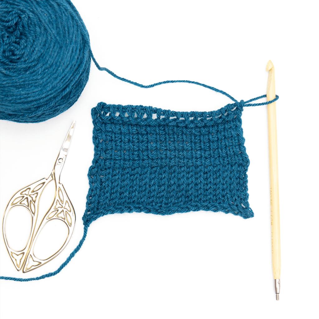 Gloss fingering yarn worked up in a tunisian crochet swatch