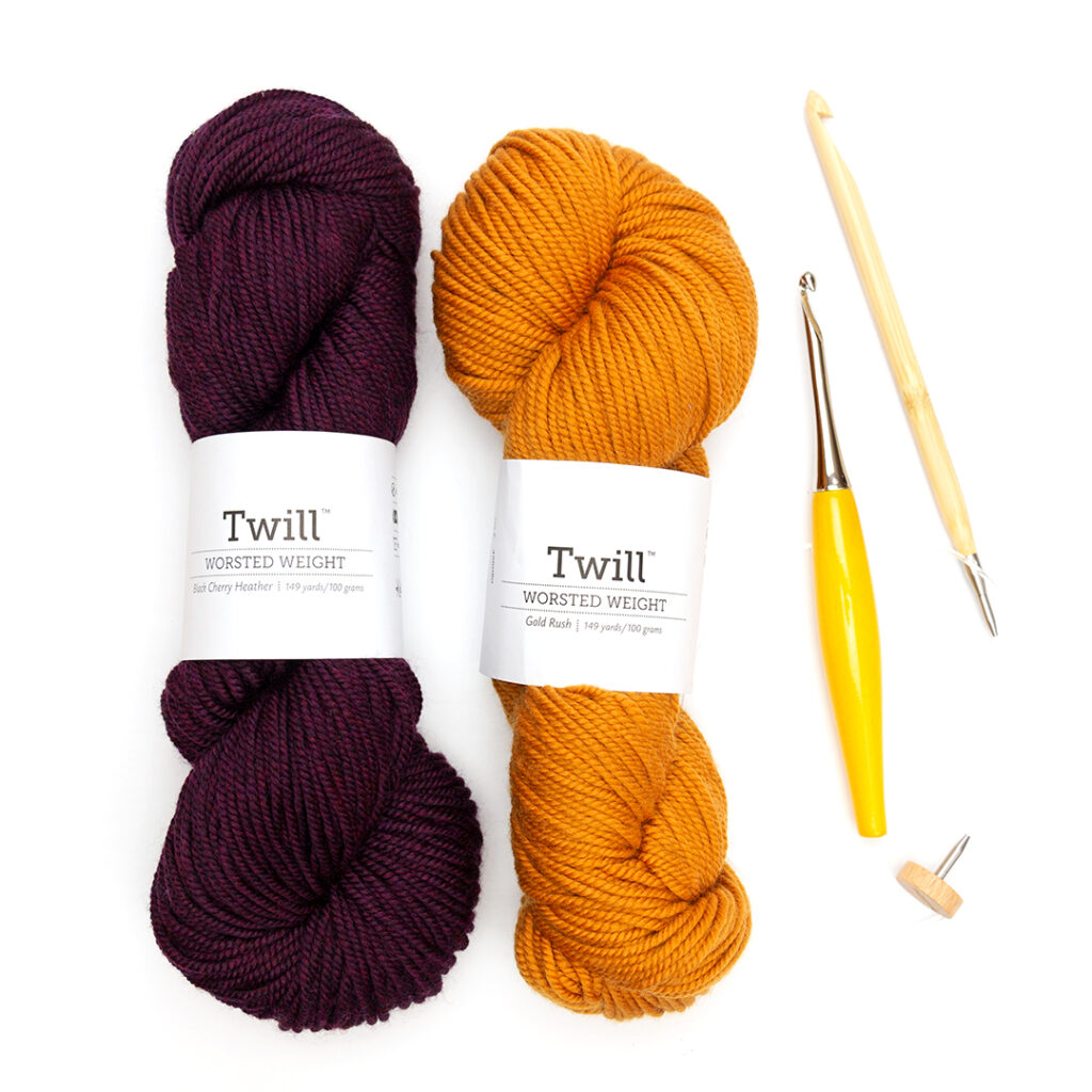 Hanks of Twill Worsted Weight in Purple and Yellow with two crochet hooks