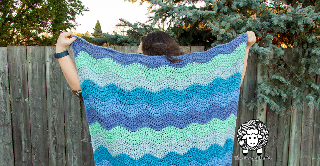 Woman holding a crochet ripple blanket up behind her.