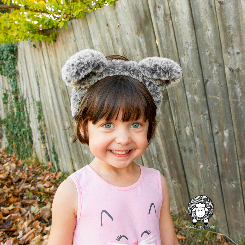 Smiling girl in a pink shirt wearing a crochet animal ears headband made with fable fur yarn