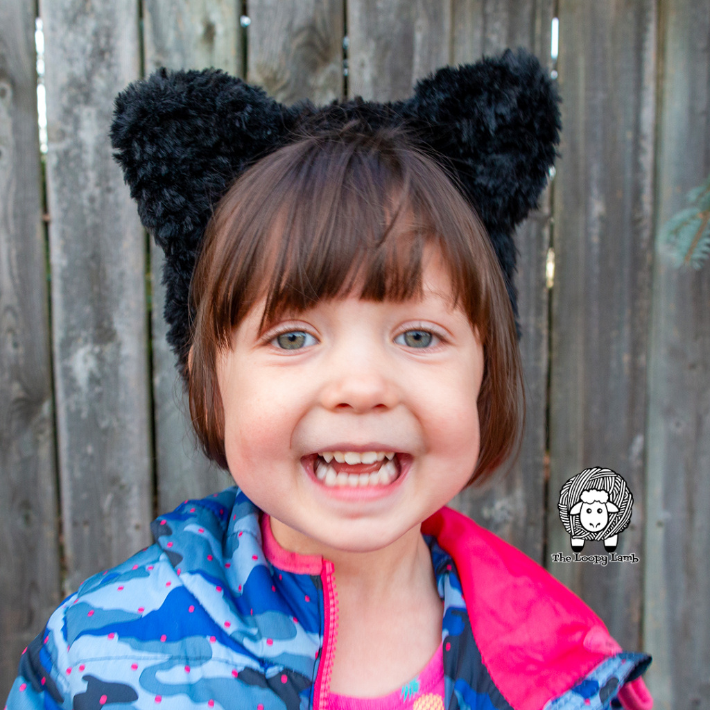 smiling girl wearing a crochet cat headband made with faux fur yarn