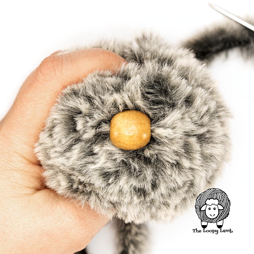 bead sewn onto side of faux fur yarn pompom