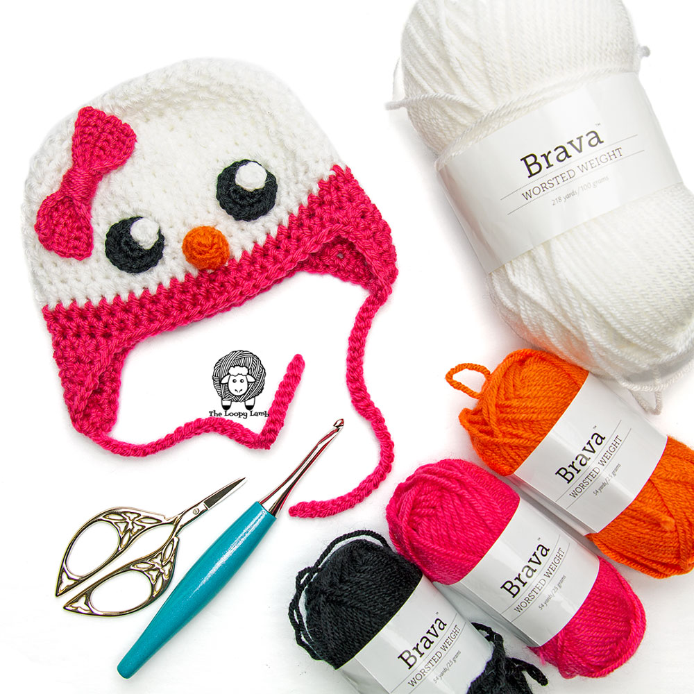 Crochet Snowman Hat in a flat lay with Brava Worsted Yarn and Furls Crochet Hook