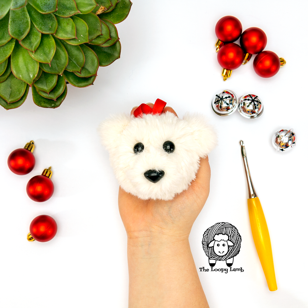 crochet bear ornament being held in a hand surrounded by christmas decorations
