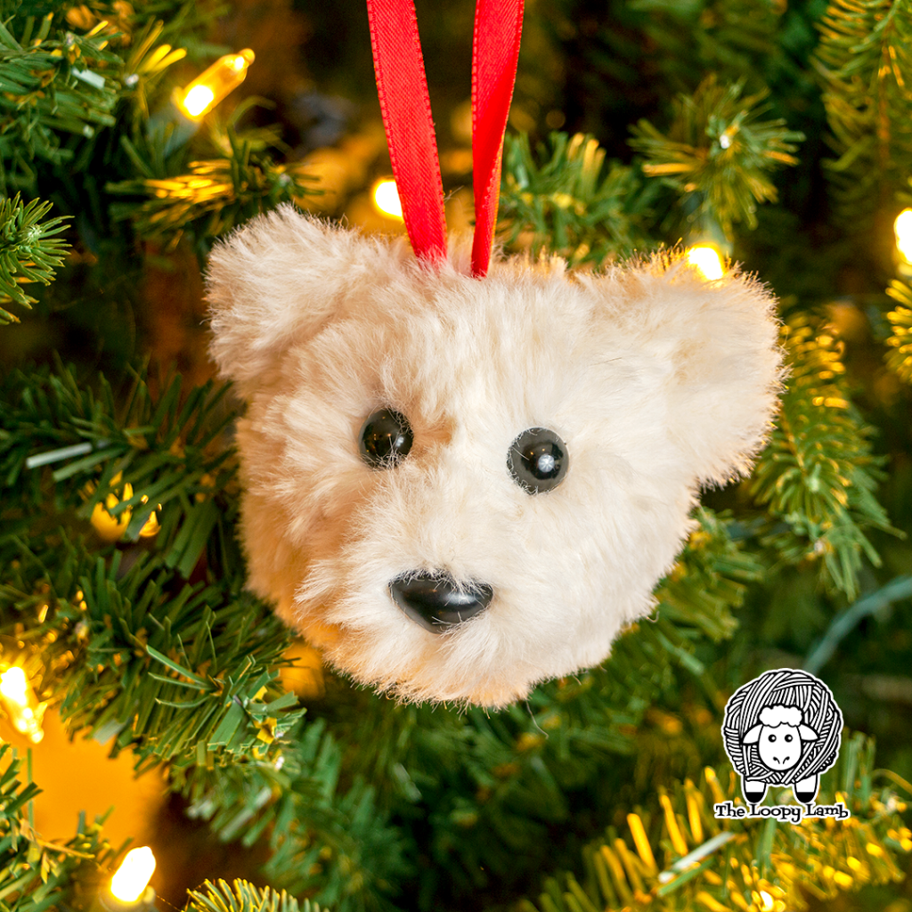 Faux fur crochet bear ornament hanging in a christmas tree