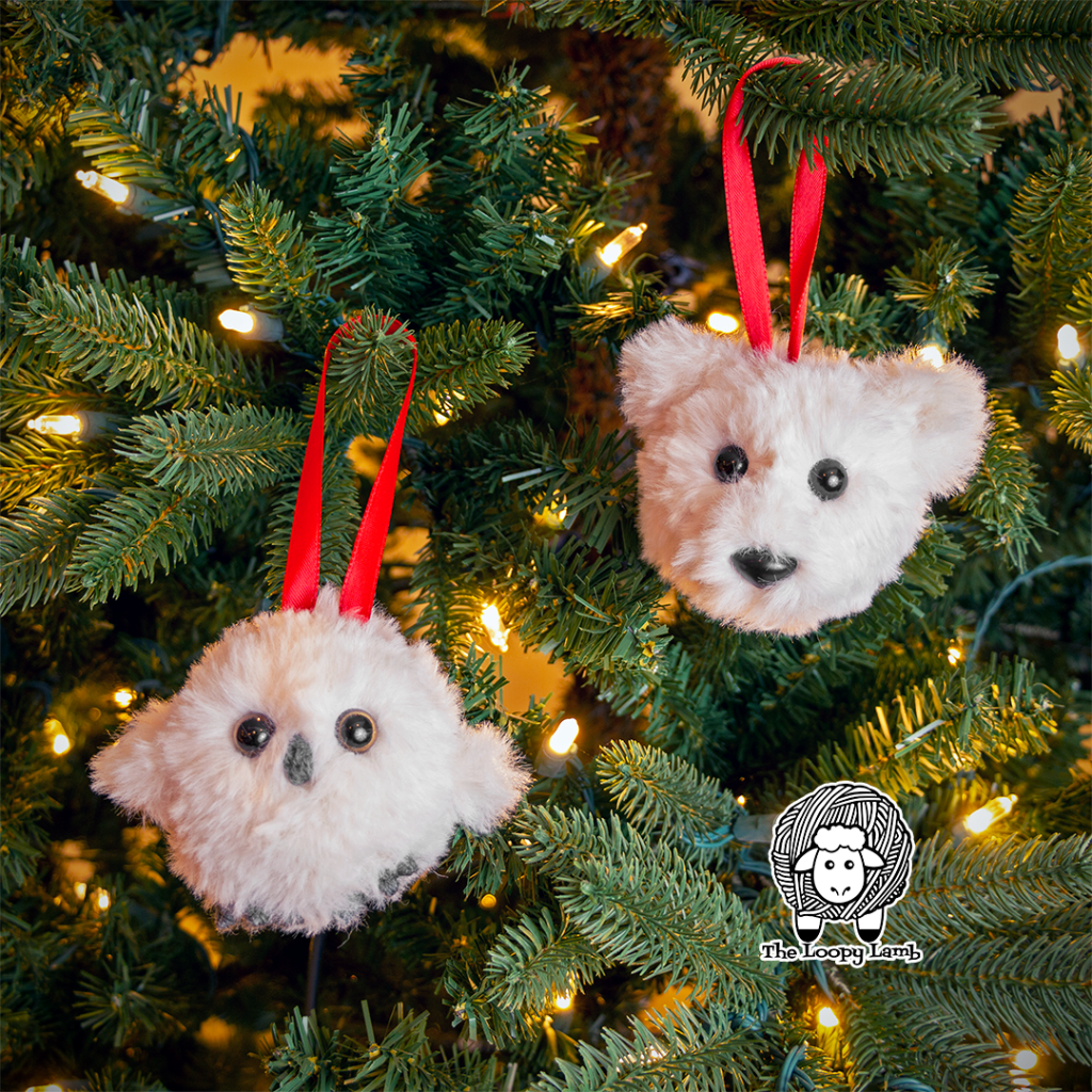 crochet owl and polar bear ornaments hanging in a christmas tree.