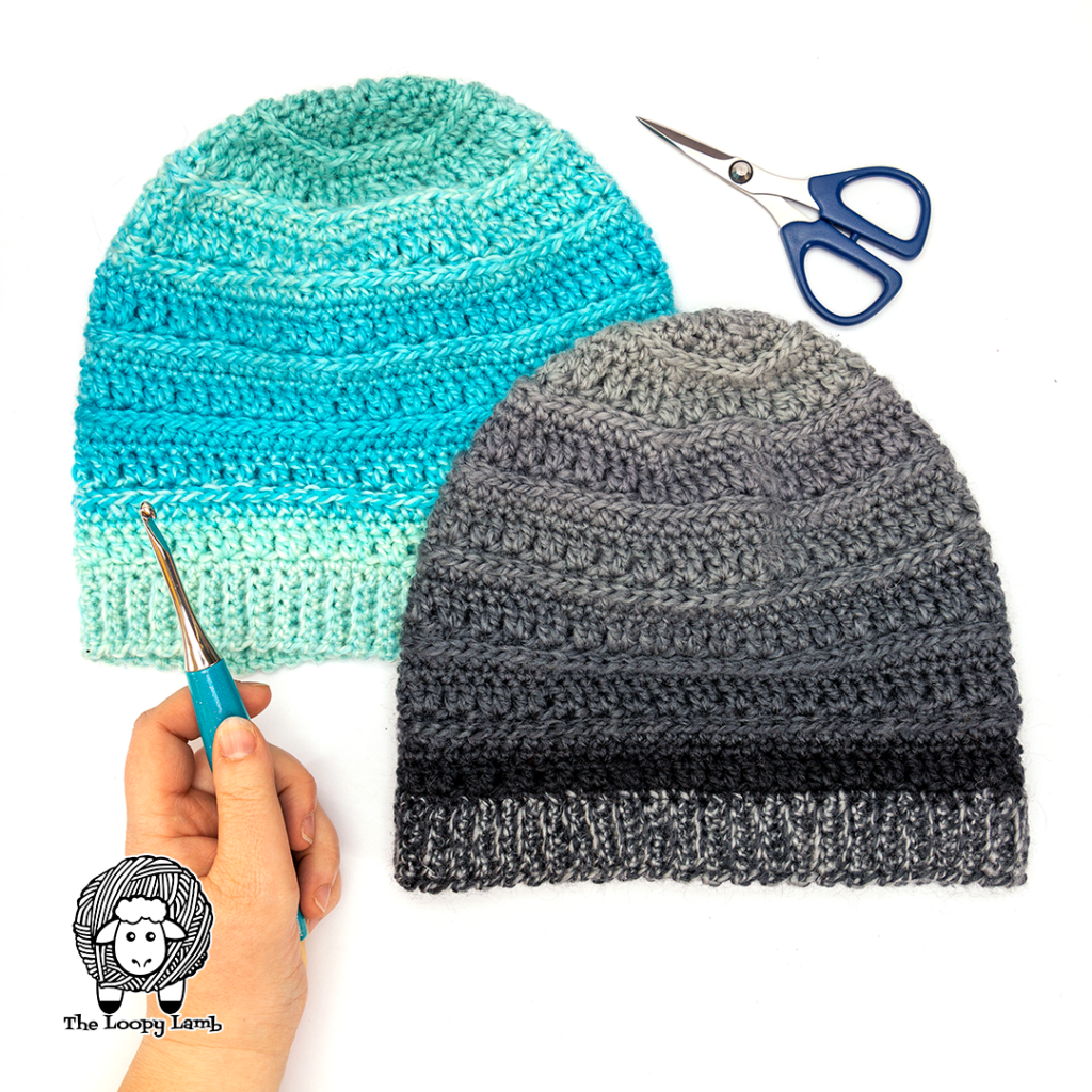 Two Into the Fade Hats in a flay lay with a Furls Odyssey Crochet hook