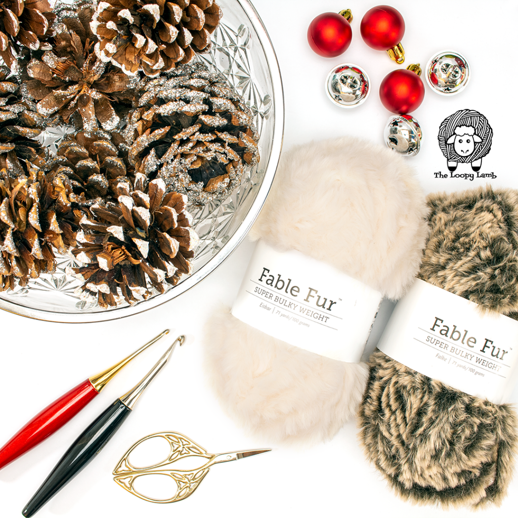 flat lay of fable fur yarn, pinecones and furls crochet hooks - materials used in this crochet christmas ornament pattern