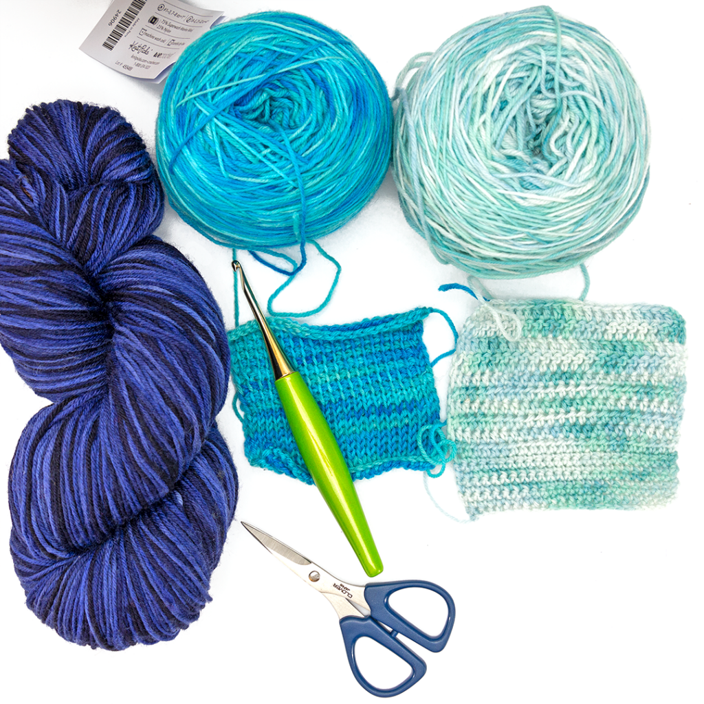 WeCrochet Stroll Tonal Yarn next to some swatches with a Furls crochet hook & Scissors