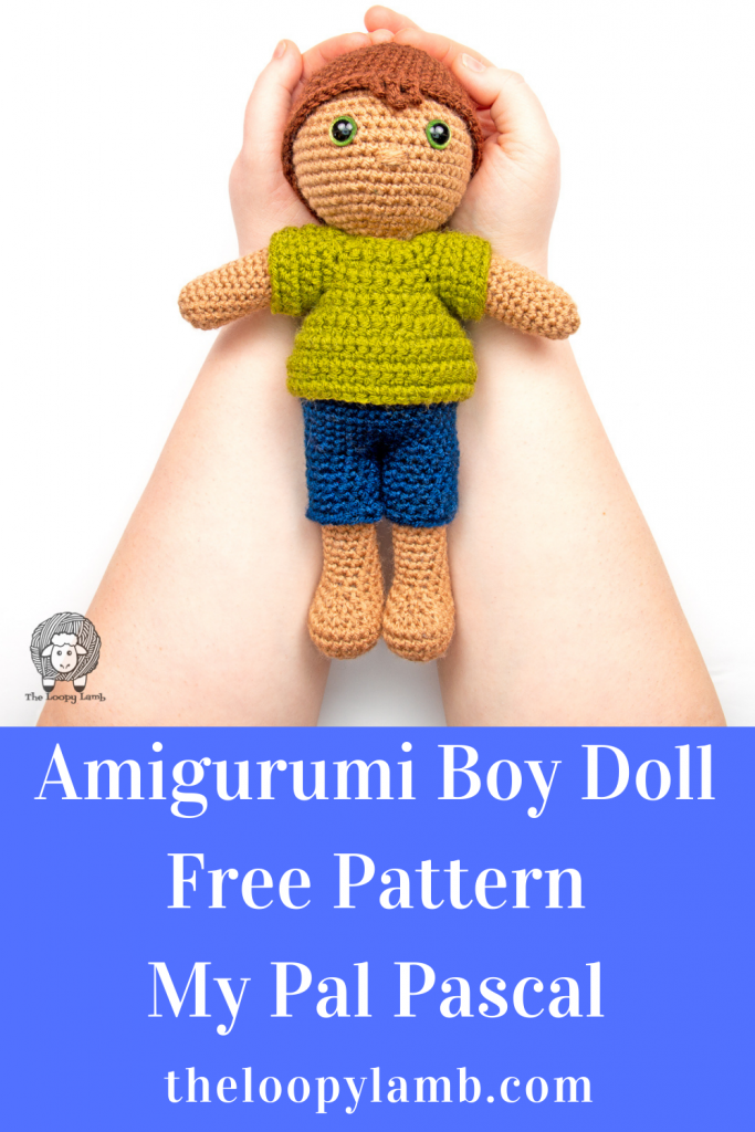 Crochet doll held in hands that was made with this Amigurumi boy doll free pattern