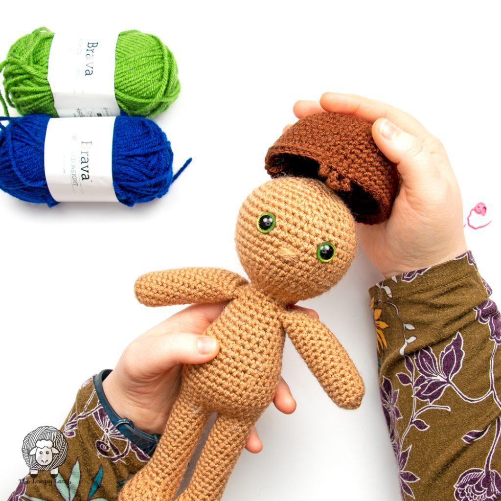 amigurumi boy doll having a hair cap placed on it's head