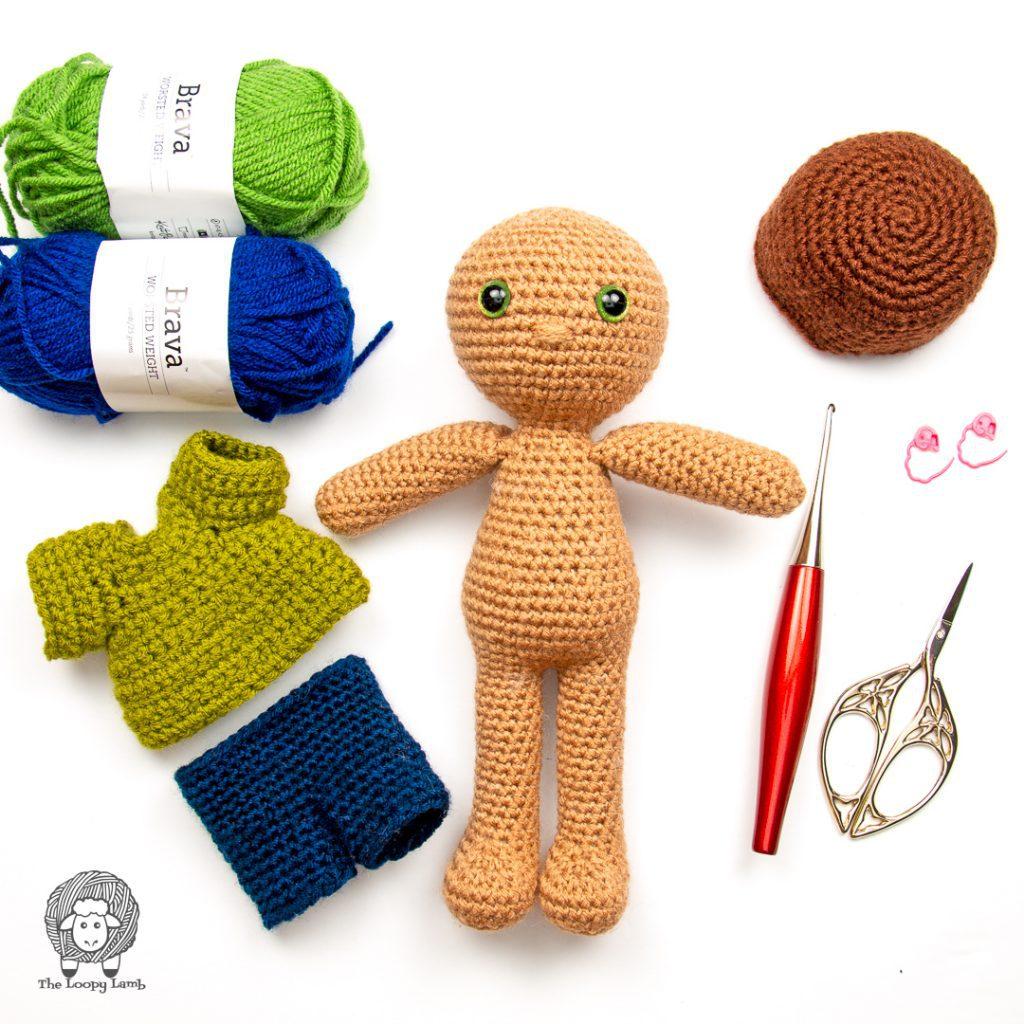 amigurumi boy doll with doll clothes in a flat lay