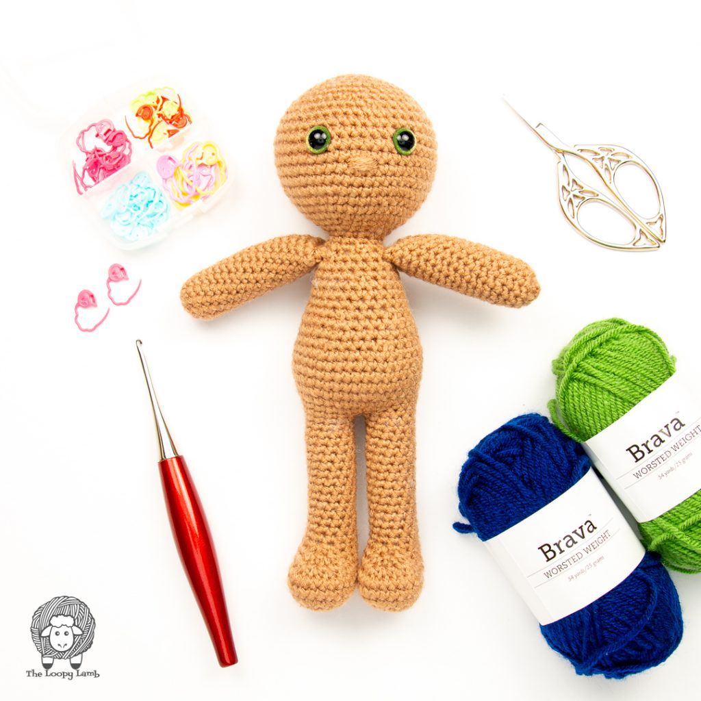 crochet boy doll in a flat lay with furls crochet hook and brava worsted weight yarn