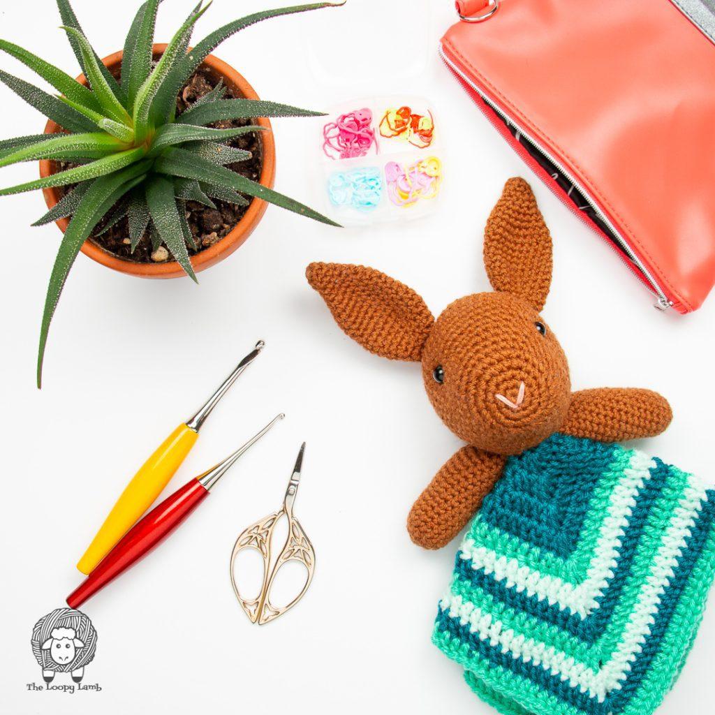 crochet bunny lovey in a flat lay with furls crochet hooks and scissors