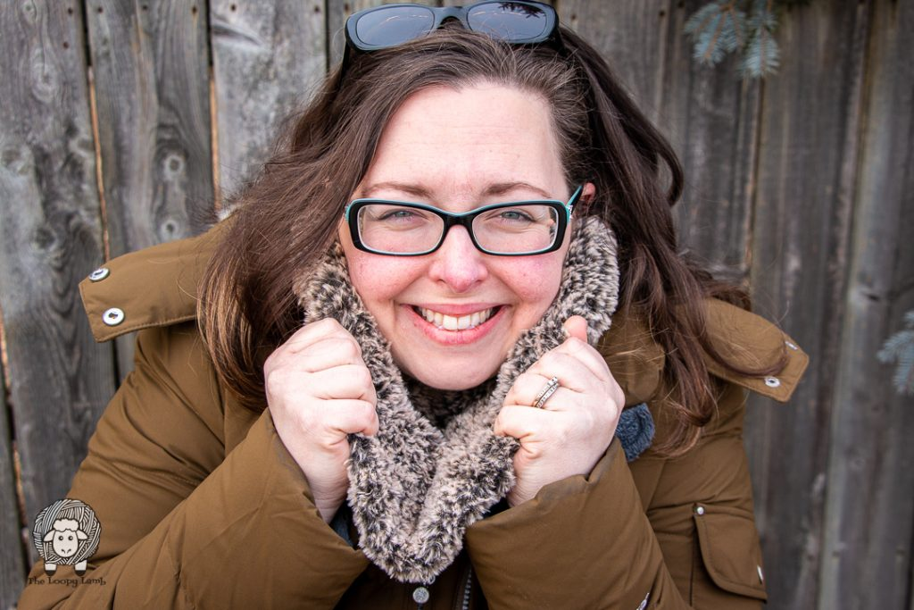 smiling brunette woman in glasses wearing a crochet cowl