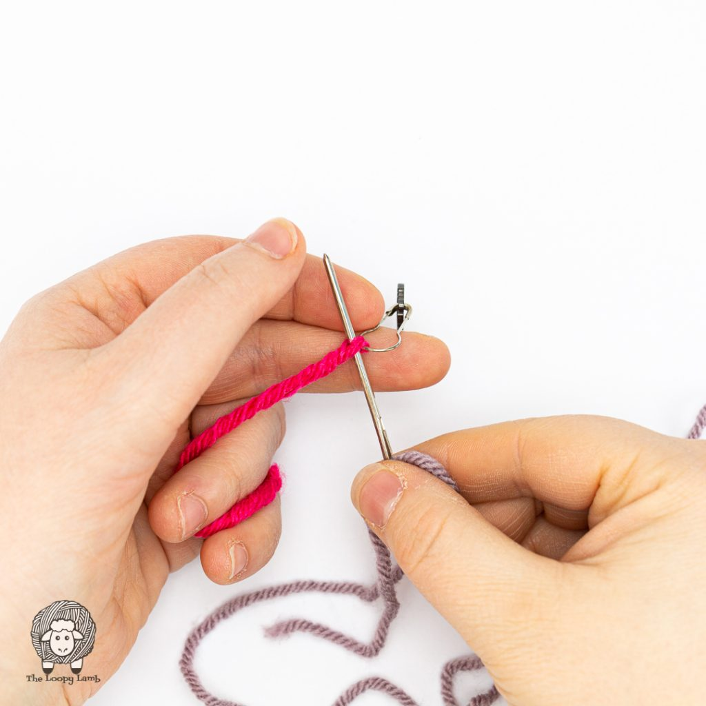 tapestry needle being fed through the yarn
