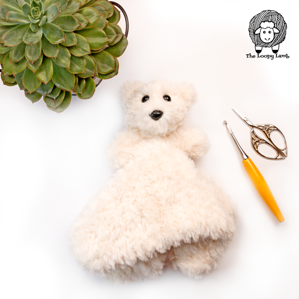 Polar bear baby lovey in a flat lay with a plant, crochet hook and scissor