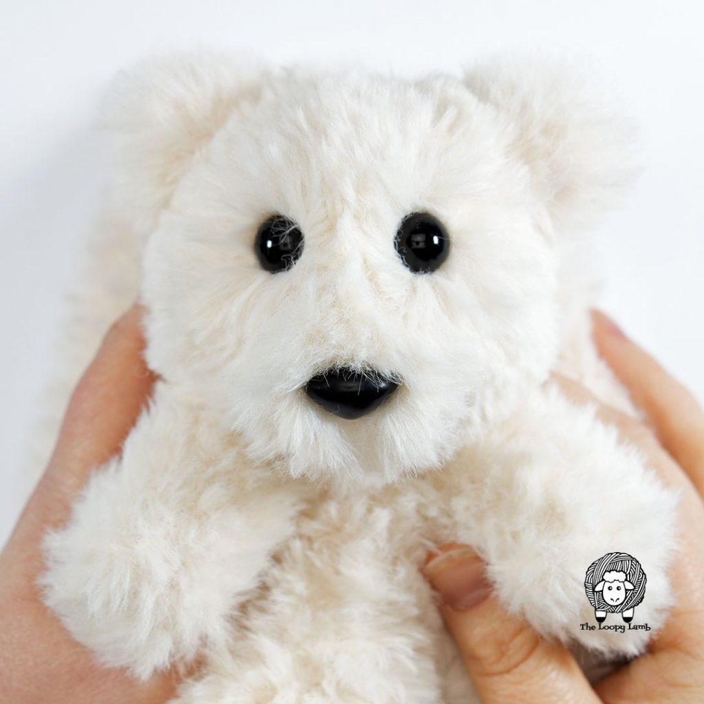 close up image of an amigurumi bear head made with faux fur yarn