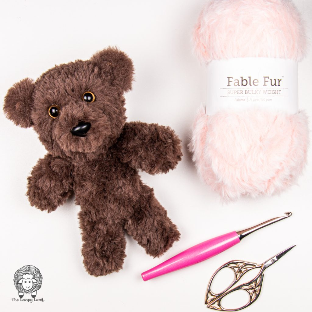amigurumi bear made with faux fur yarn, next to a ball of fable fur and a furls crochet hook