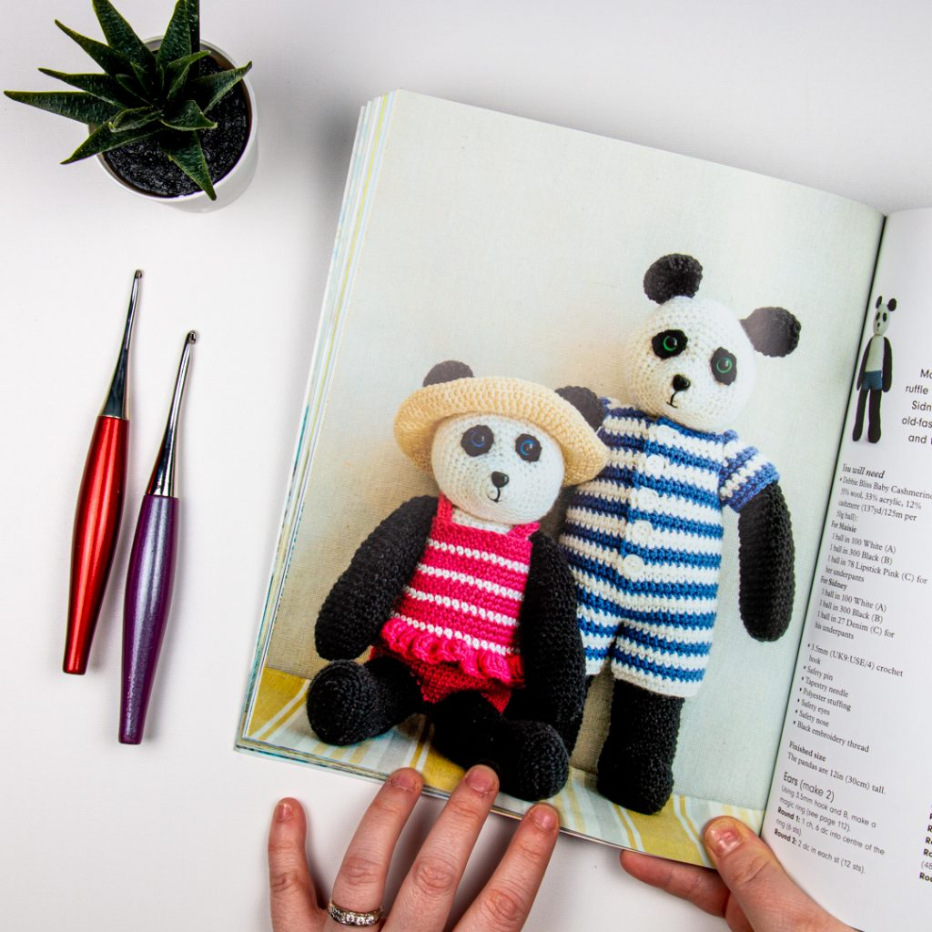 Two amigurumi pandas in a book, next to some furls crochet hooks