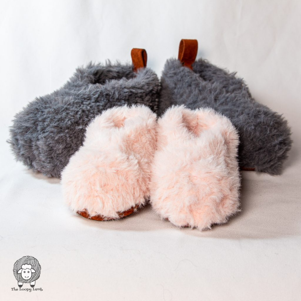 two pairs of rustic fur slippers next to eachother, one pink, one grey