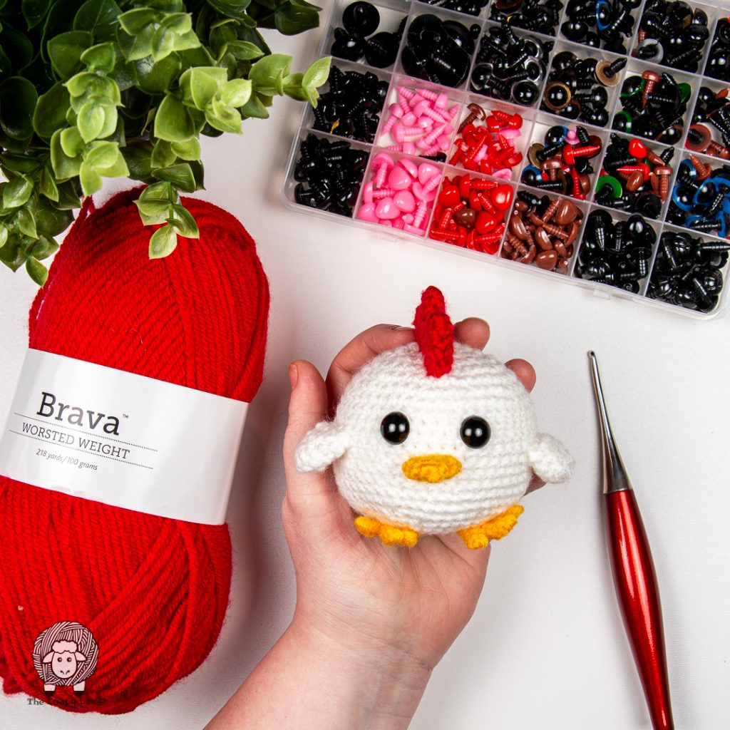 Amigurumi chick being held in a hand next to a Furls odyssey crochet hook and brava worsted yarn
