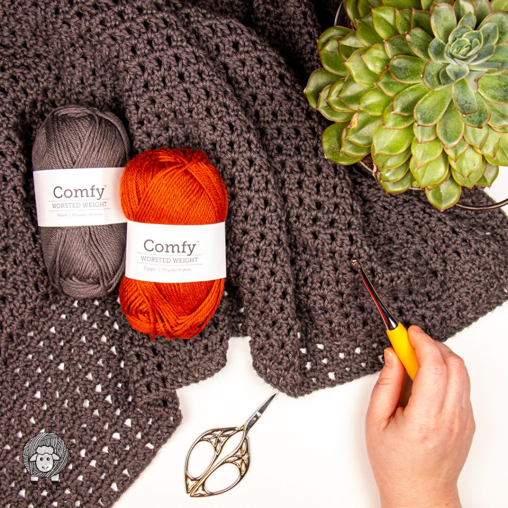 Comfy worsted yarn on a grey crocheted fabric with a hand holding a furls odyssey hook
