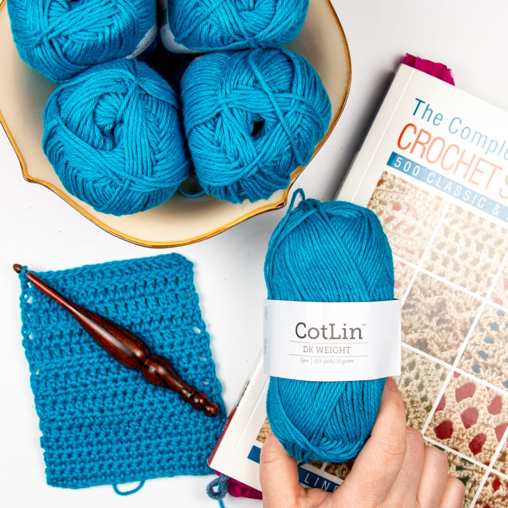 hand holding a ball of cyan cotlin with a crochet swatch and furls crochet hook