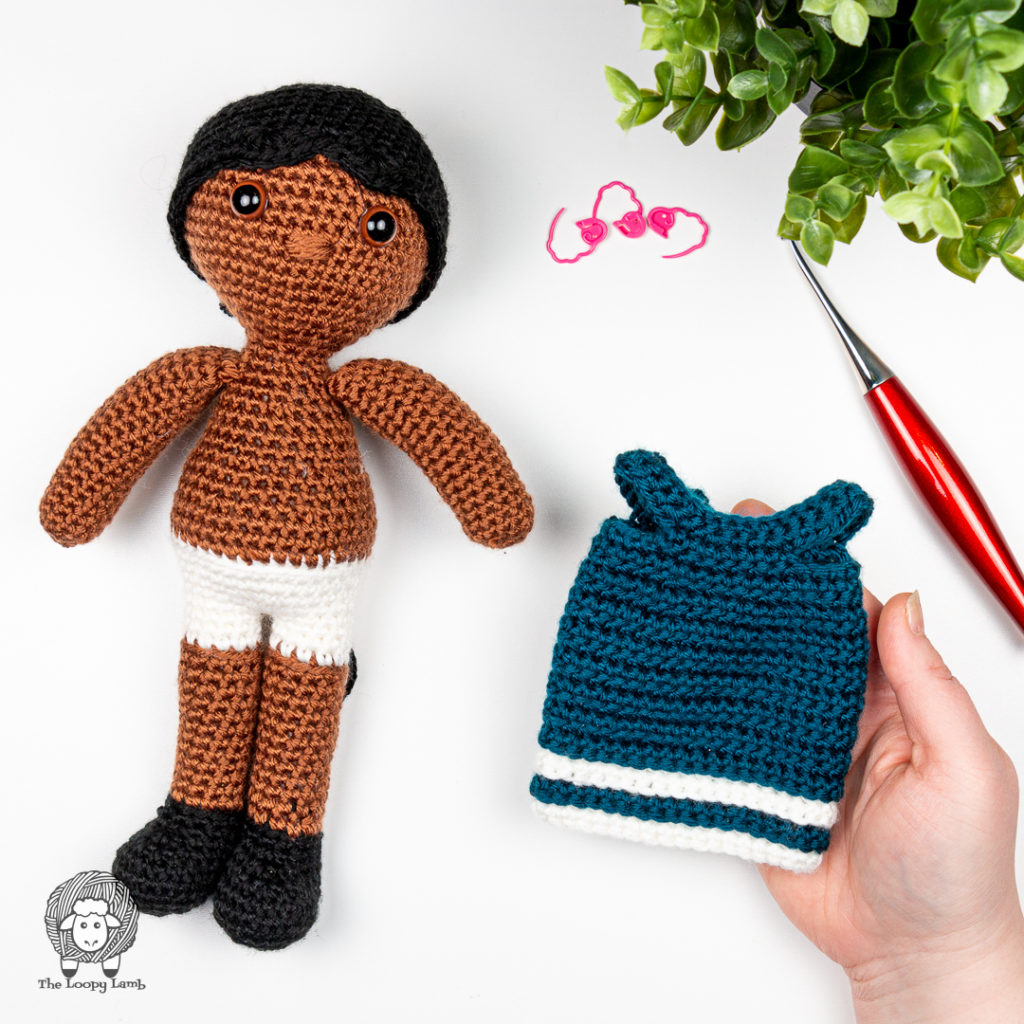 hand holding the doll dress used in this amigurumi doll with clothes pattern