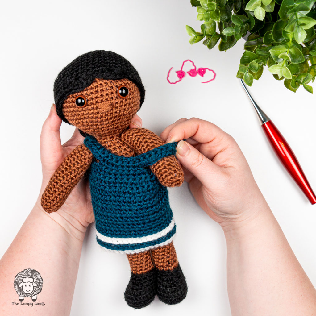 hands putting a dress on an amigurumi doll made with skein tones yarn