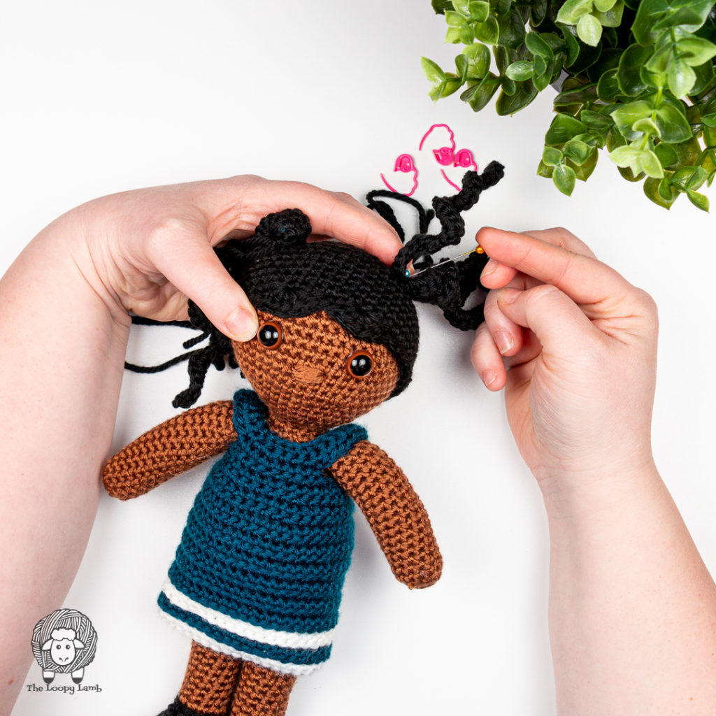hands assembling the pigtails on the crochet toy