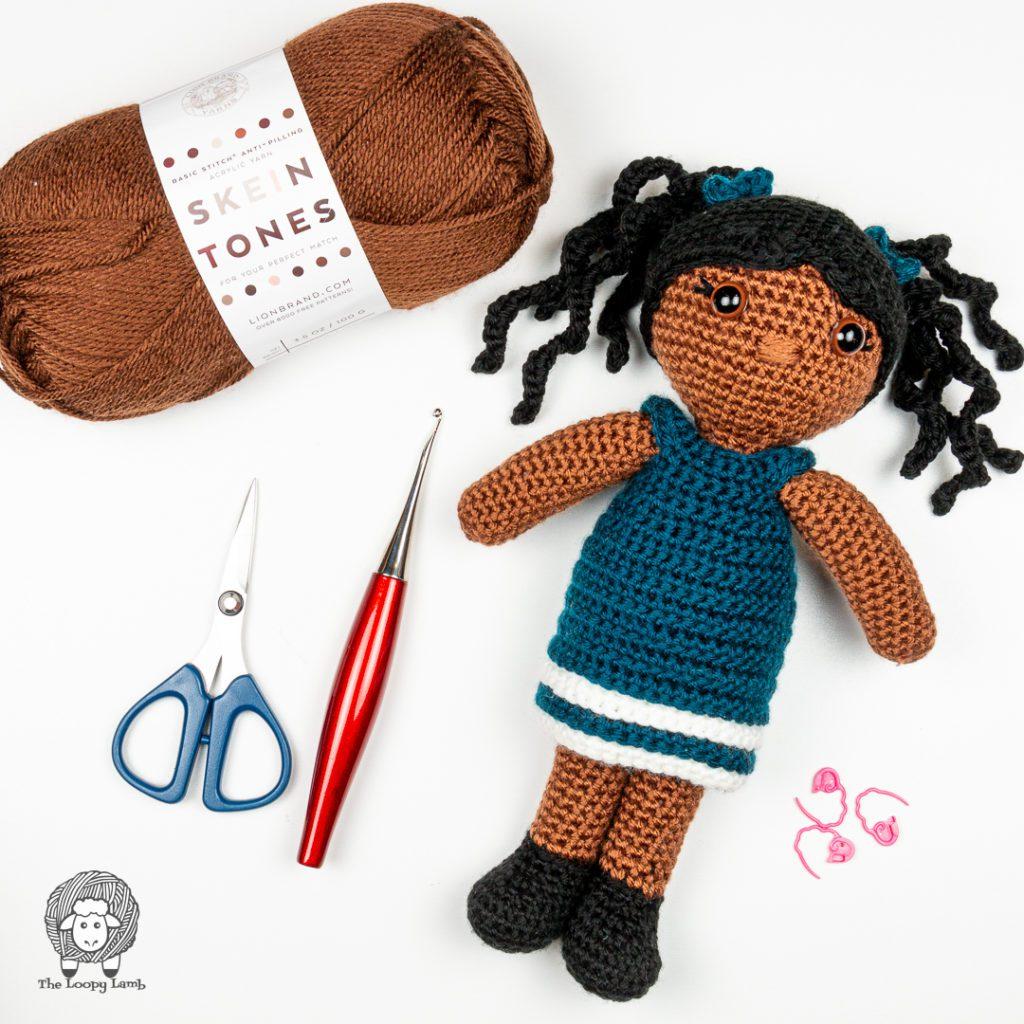 Amigurumi doll in a flat lay with a furls crochet hook
