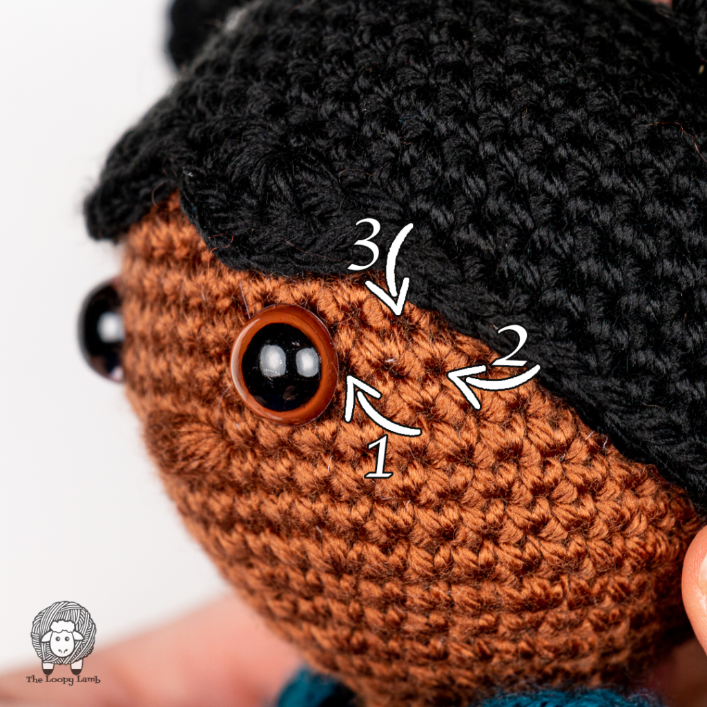 Close up image of the amigurumi doll face with numbers and arrows on it showing where to embroider the eyelashes
