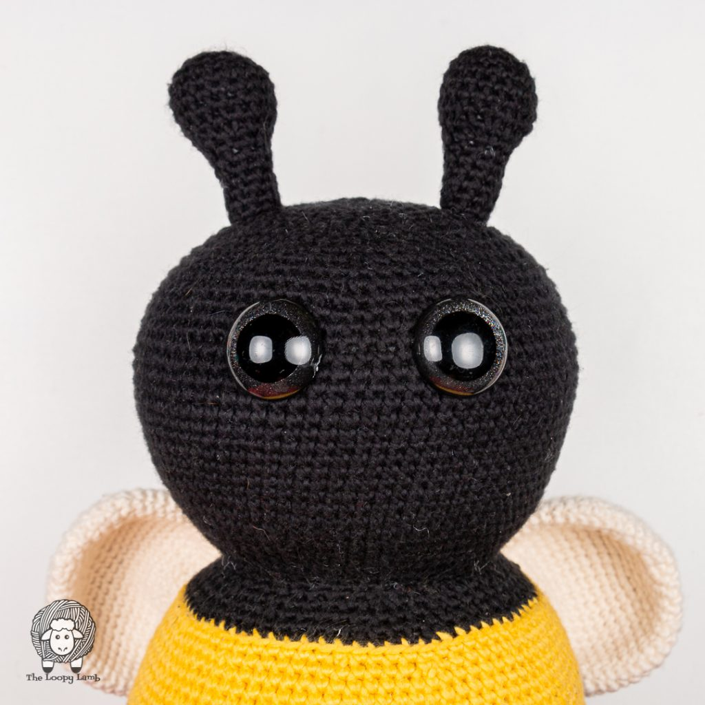 close up image of the eyes and face of the amigurumi bumblebee made with this free crochet bee pattern