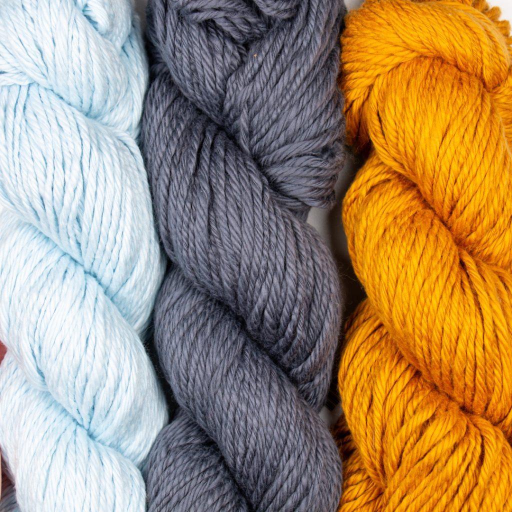 three hanks of WeCrochet Billow yarn in light blue, dark blue and mustard