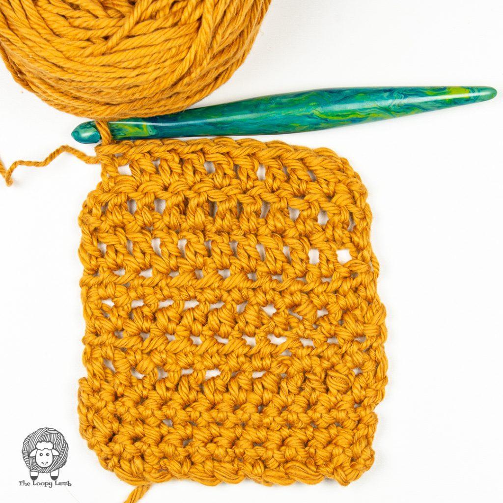 WeCrochet Billow Yarn worked up in a crochet swatch with a furls streamline swirl crochet hook