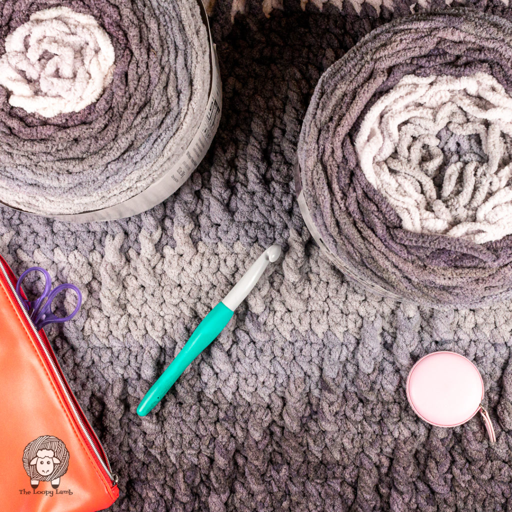 Crochet baby blanket with balls of bernat blanket ombre and a crochet hook sitting on top.
