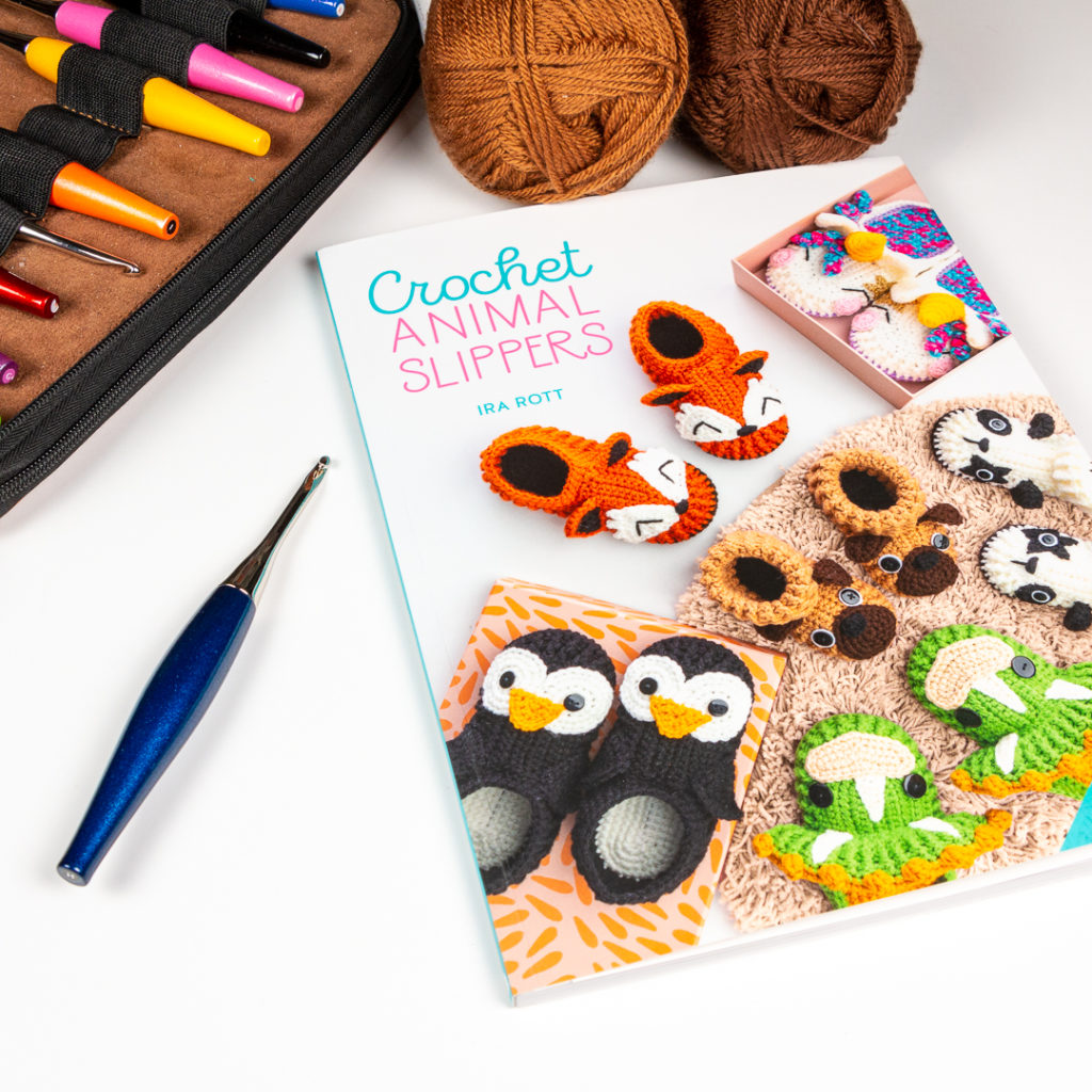 copy of crochet animal slippers in a flat lay with crochet hooks and yarn