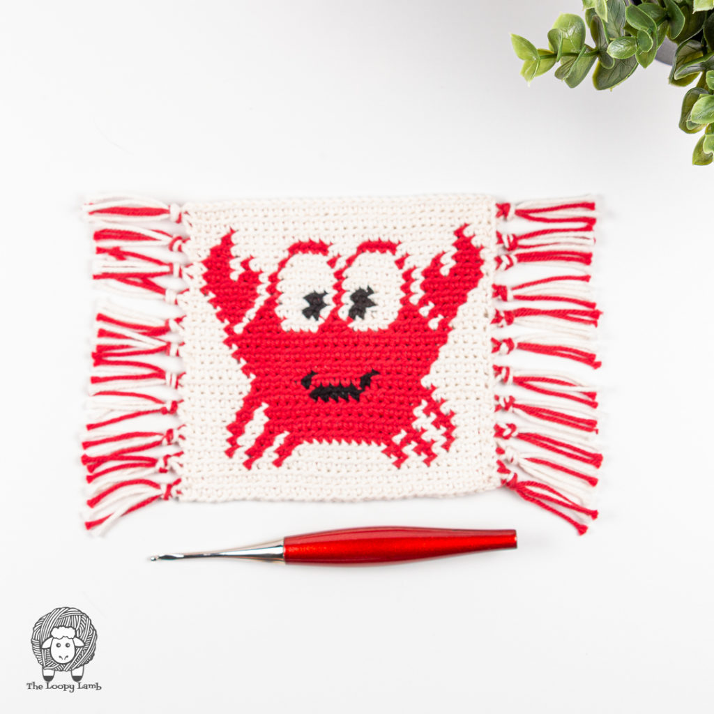 crochet mug rug with a crab on it made with this crochet crab mug rug free pattern.