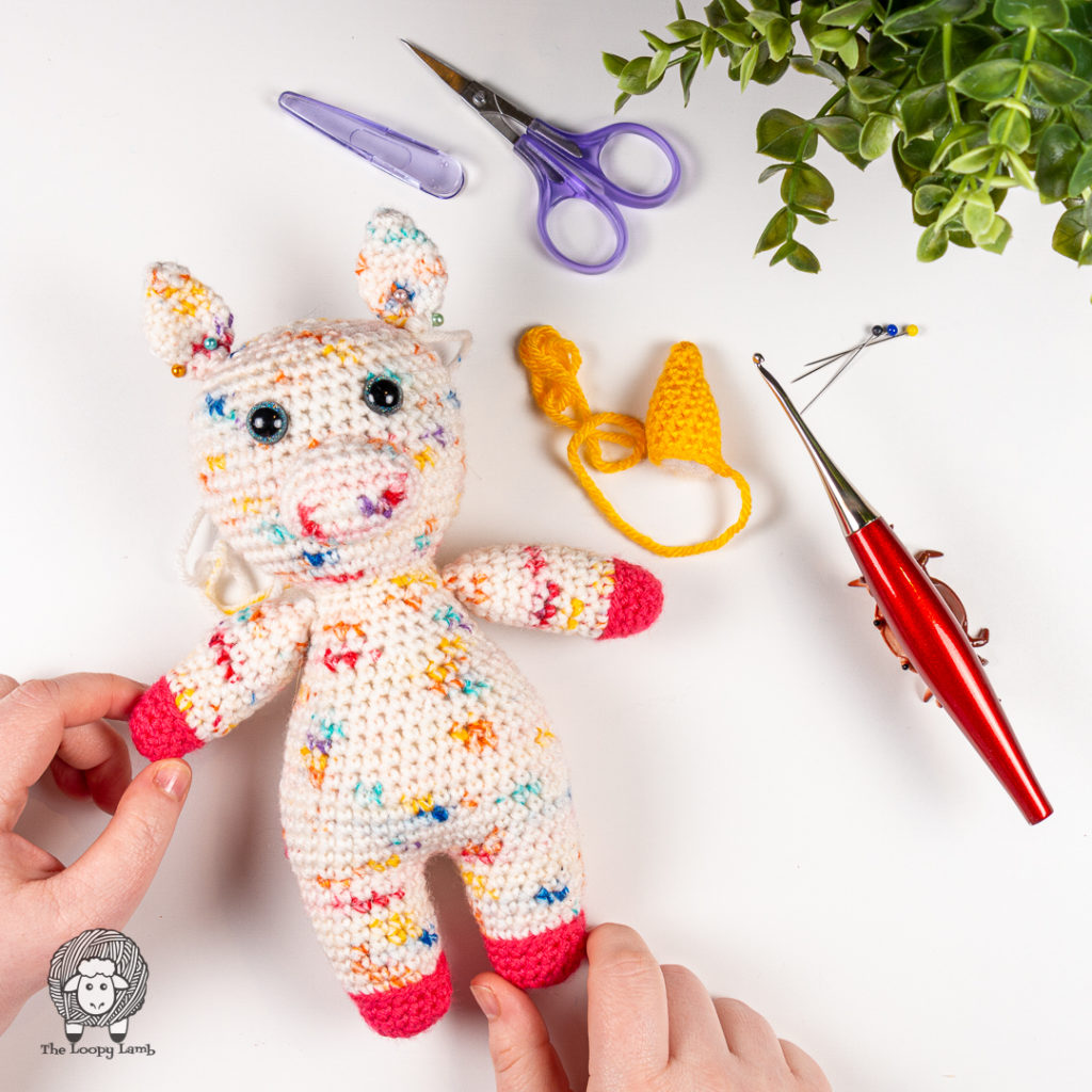 amigurumi unicorn, made with this free crochet unicorn pattern in a flat lay with a furls crochet hook