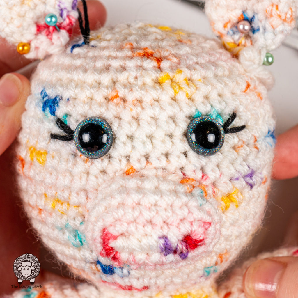 Completed embroidered eyelashes on a crochet toy face