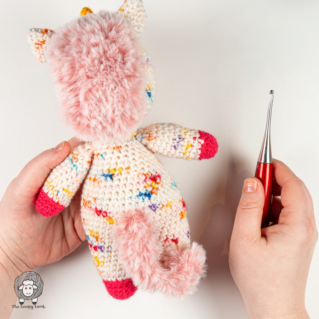 view of the back of this amigurumi unicorn design, showing.a furry tail and mane