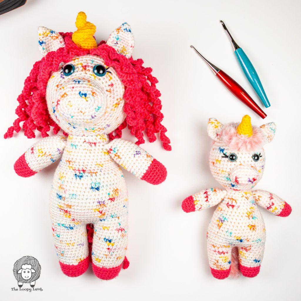 large amigurumi unicorn next to the mini unicorn made with this free crochet unicorn pattern