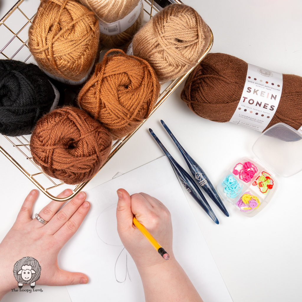 Balls of skin toned yarn called skein tones in a basket while person draws a on a piece of paper