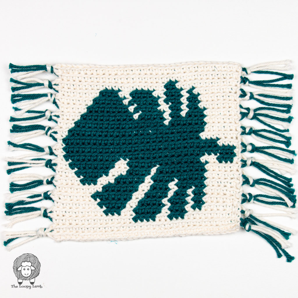 crochet coaster that looks like a miniature rug with an image of a green monstera leaf on it and green and white fringe on the sides