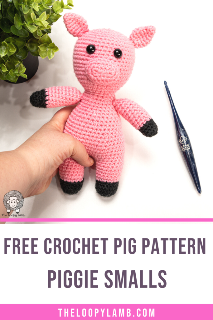 Amigurumi pig held in a hand with text saying free crochet pig pattern