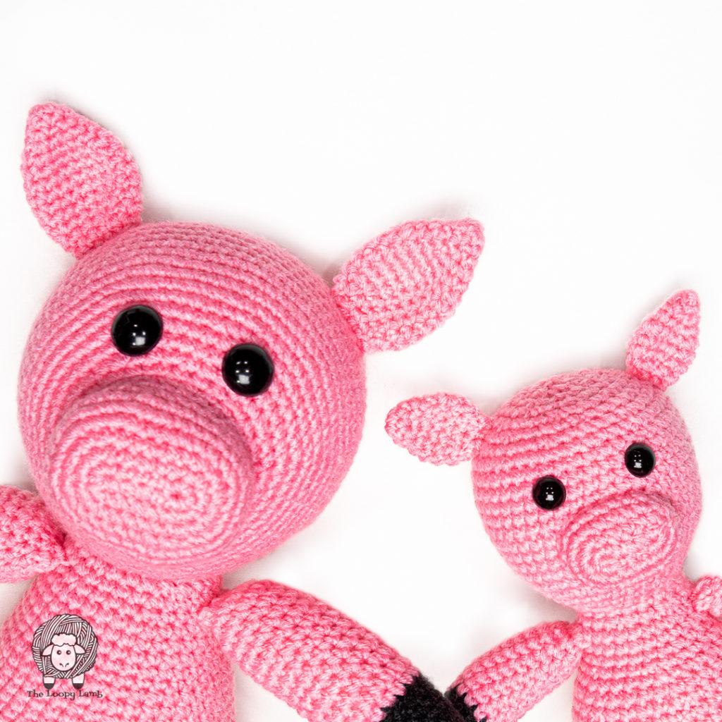 two crochet pigs next to each other on a white background