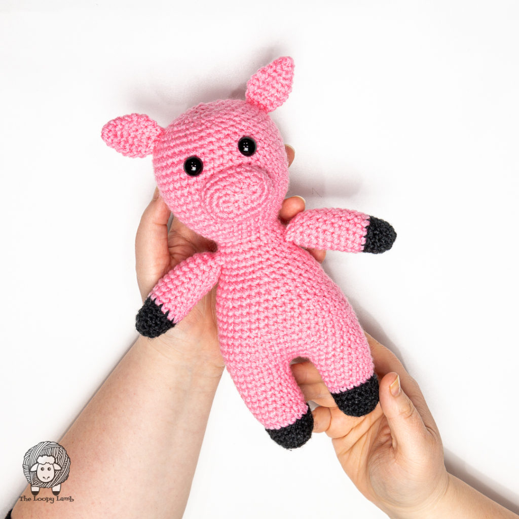 hands holding an amigurumi pig made with this free crochet pig pattern