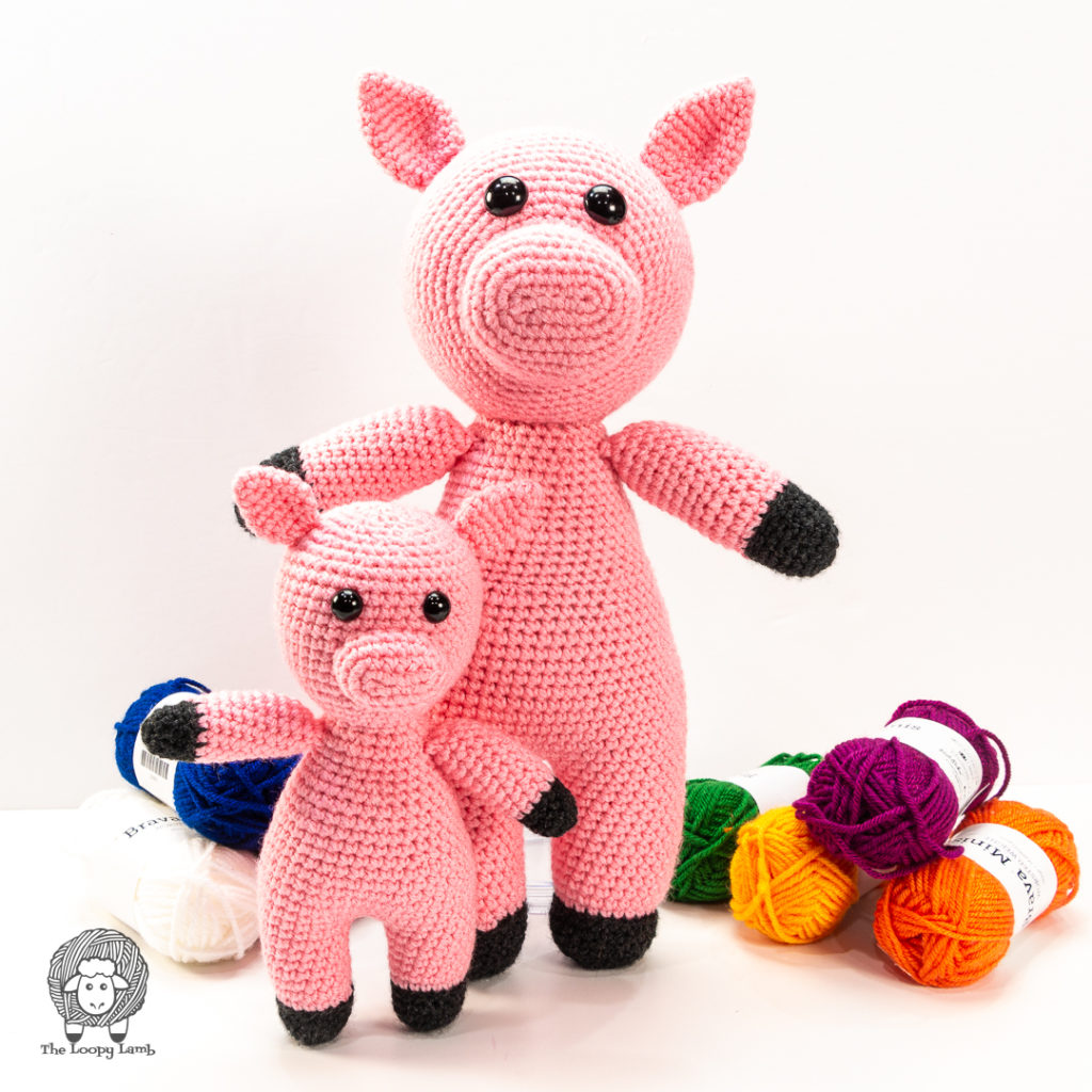 Amigurumi pigs in two different sizes standing side by side