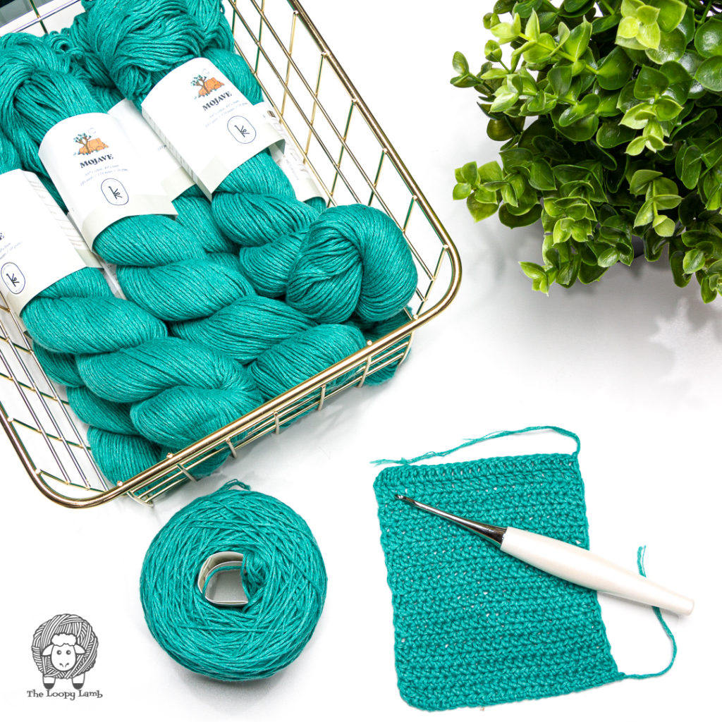 turquoise cotton/linen blend yarn in a flat lay with a Furls Crochet Hook